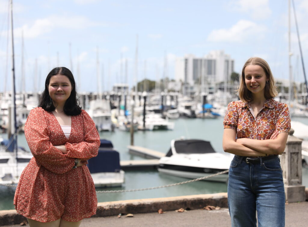 Two young women stand in front of a marina in Townsville